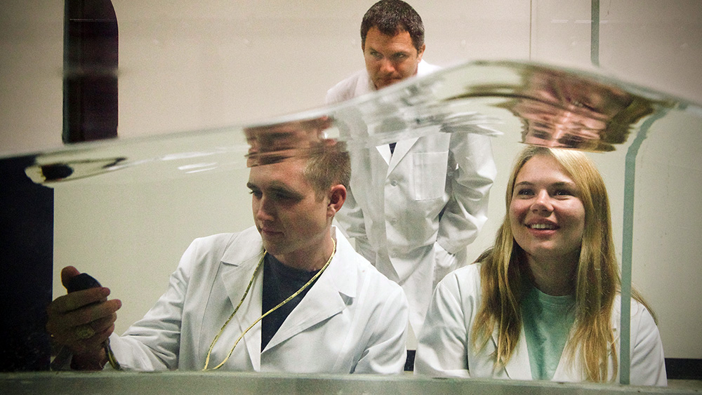 A professor monitors two graduate students while conducting a test in the wave tank simulator.