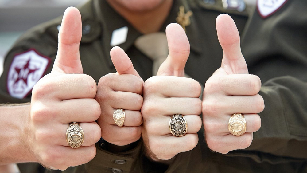 Four thumbs up with each wearing an Aggie ring.