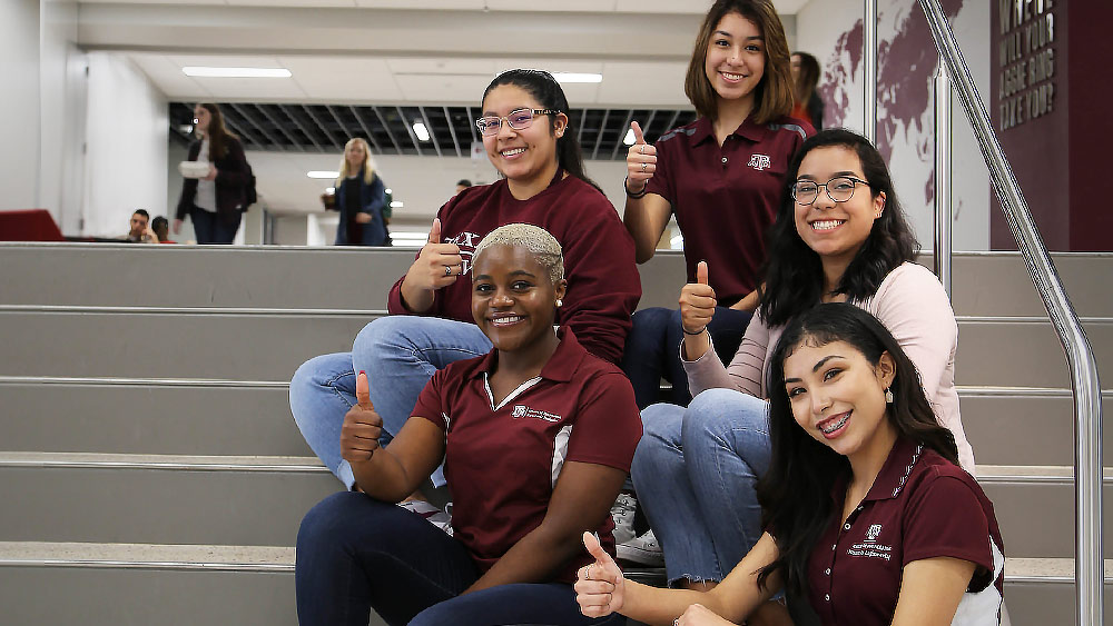 Aggie women engineering graduates holding up Gig-Em signs