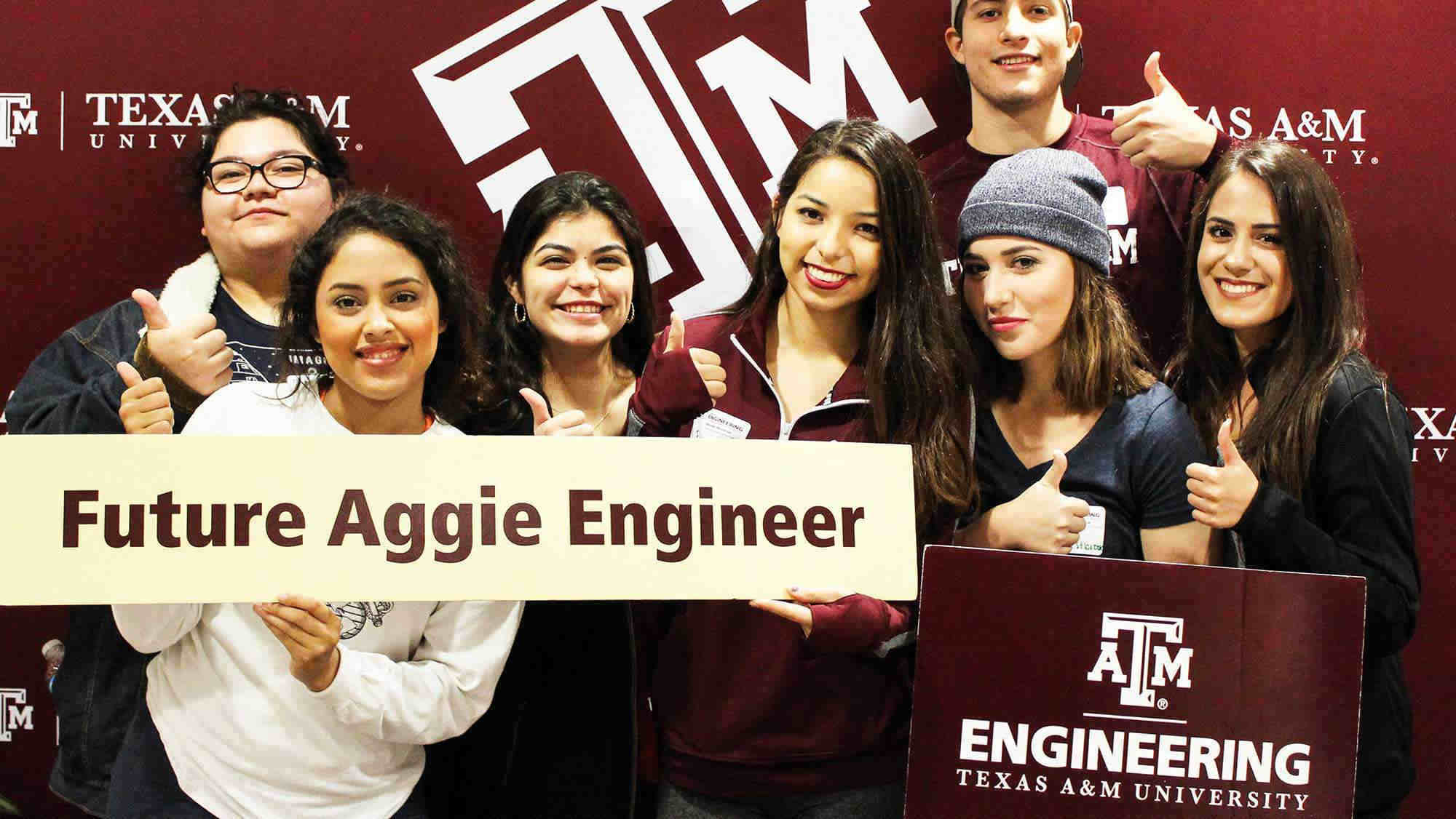 Texas A&M University in the background with seven students with their thumbs up holding a sign that says Future Aggie Engineers and Engineering Texas A&M University