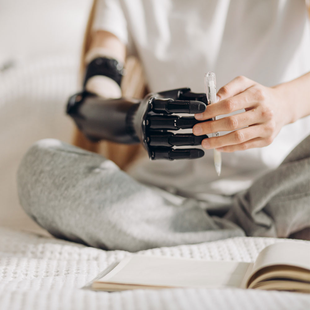 Woman with a prosthetic arm sitting cross-legged on a bed and holding a pen with both hands, over a notepad.