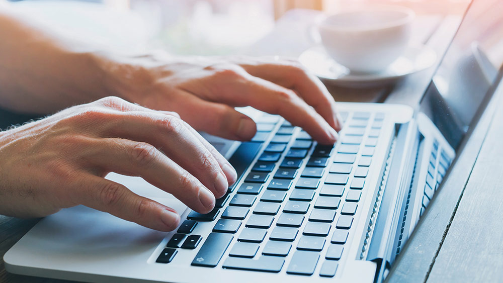 person typing on laptop keyboard