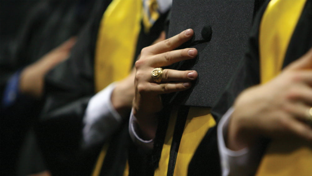 Student at graduation close up of their Aggie ring.