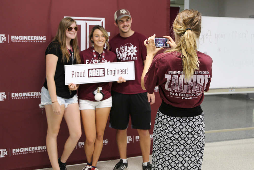 group taking a photo together in front of TAMU maroon backdrop
