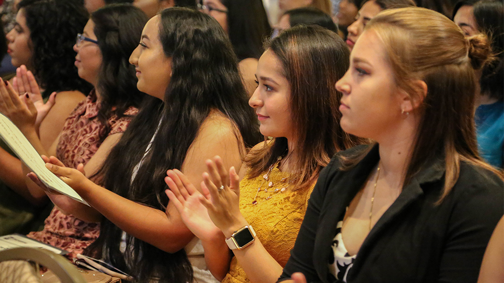 Female students clap in audience