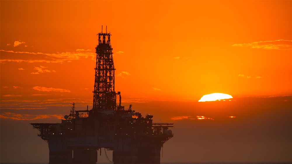 An ocean drilling rig at sunset.