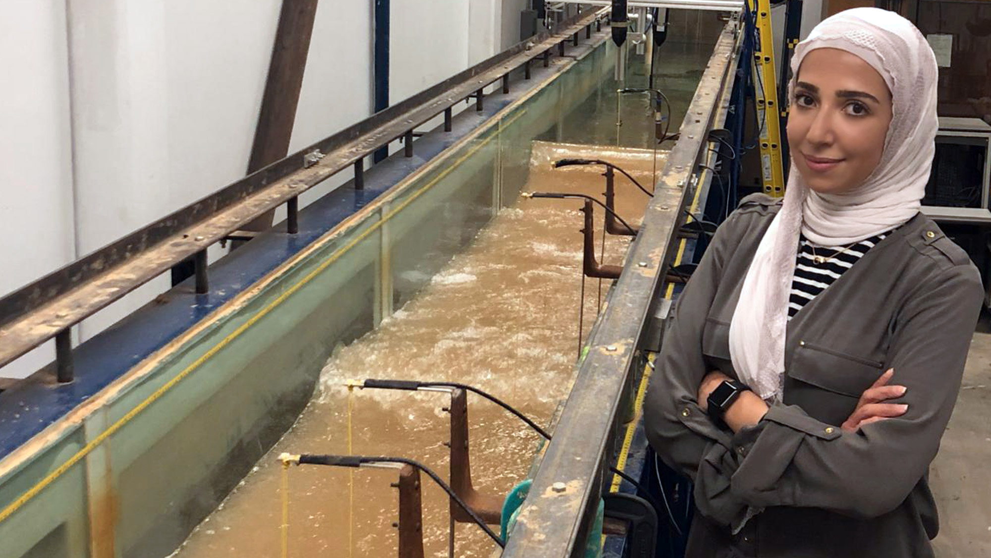 Badreyah Al-Marshed stands next to a wave tank to conduct testing for her research project.