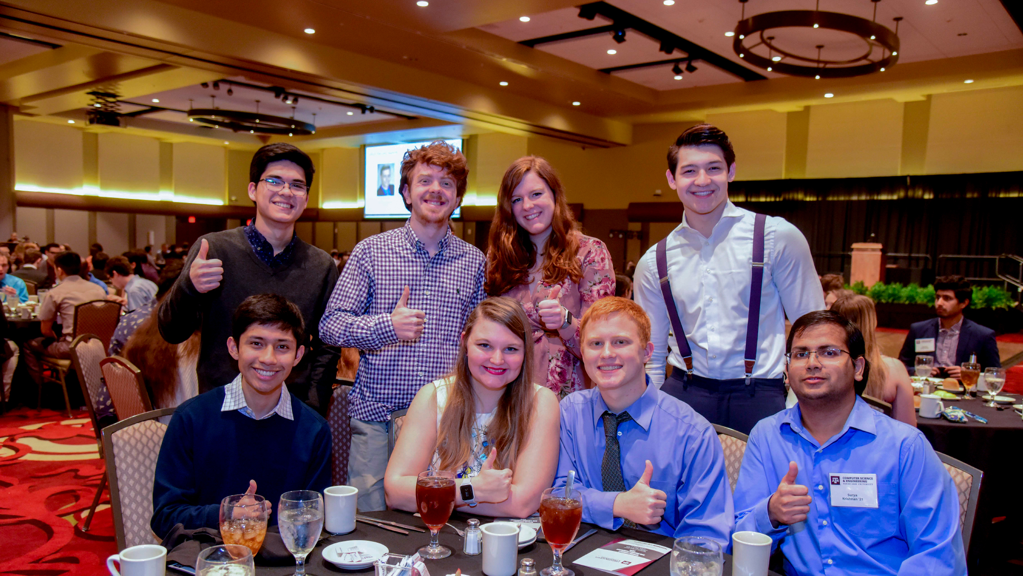 A group of students at the spring banquet dinner giving a Gig 'Em sign.