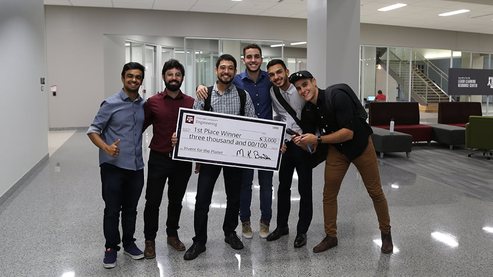 6 teammates from Brazil hold a check that says $3,000 - 1st place winner