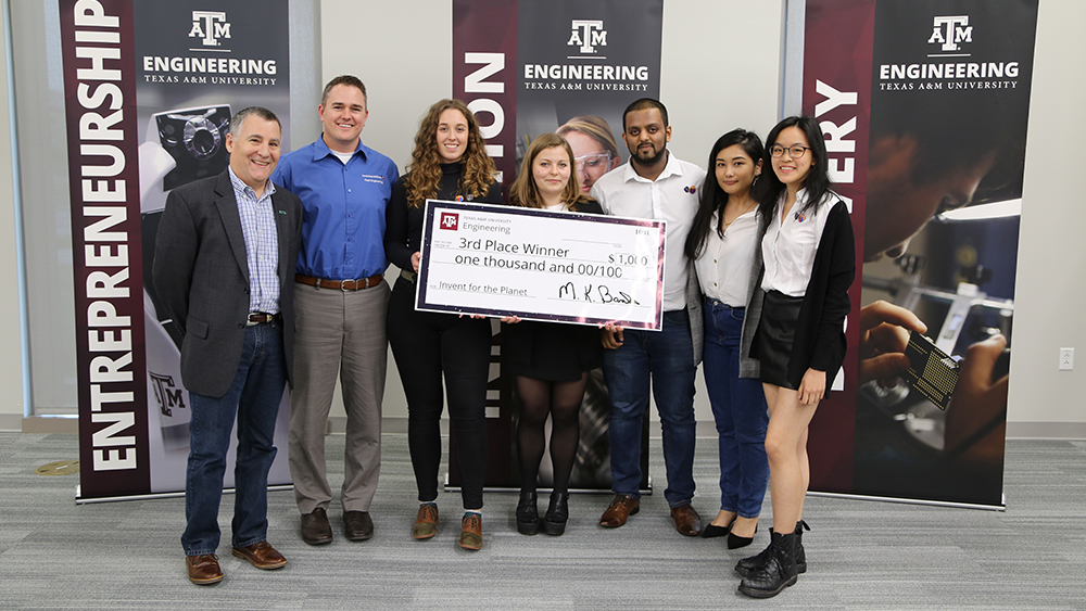 Members of SuperSocials from Swansea University pose for a photo with two judges and a check for $1,000.