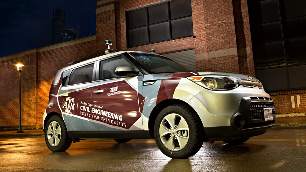 Autonomous vehicle is parked in front of a building with the Department of Civil and Environmental Engineering logo across the passenger front and back doors.