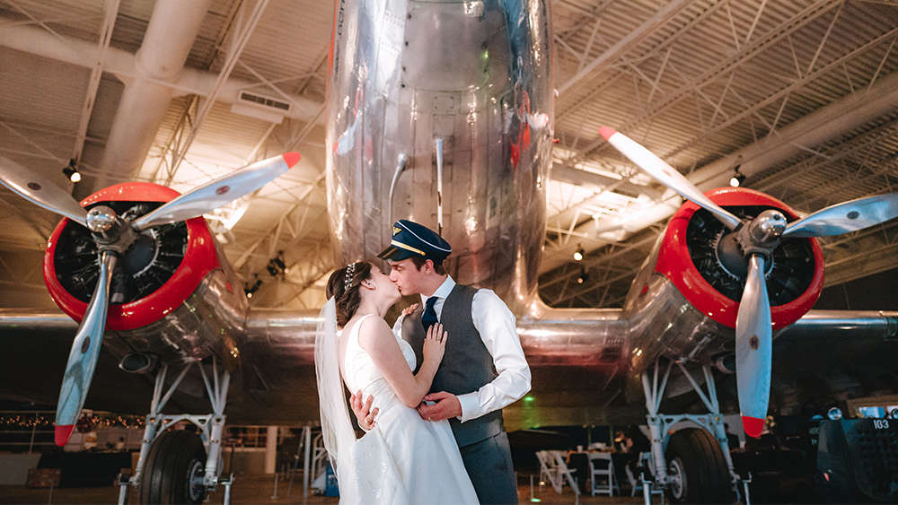 Katie and Steven, former aerospace engineering students, are dressed in their bride and groom wedding attire. Katie is wearing a white bridal gown with veil and Steven is wearing a dark gray vest, white collared shirt and navy blue tie along with a navy blue and gold pilots hat. Steven is holding Katie in his arms as her kisses her under the nose of a restored DC-3 aircraft of silver and red color.