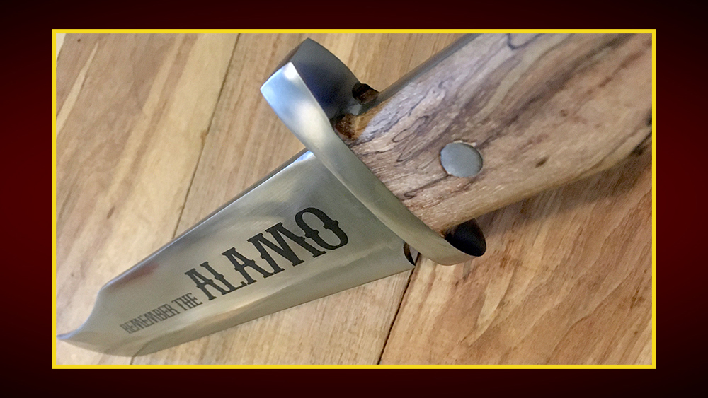 "A bowie knife with its sharp edge pointing away. It has a wooden handle and the words ""Remember the Alamo"" etched into the blade."