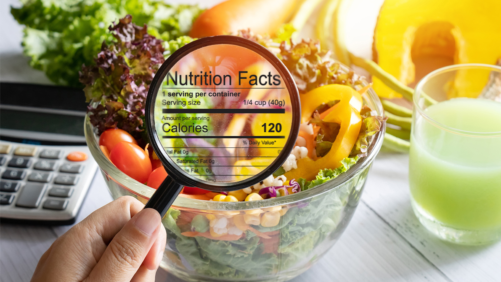 Table of food. Overlaying it is a magnifying glass looking at nutritional content