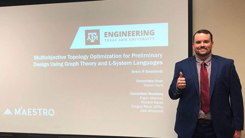 Brent Bielefeldt in a professional suit, posed next to a project screen showing the opening slide of his dissertation.
