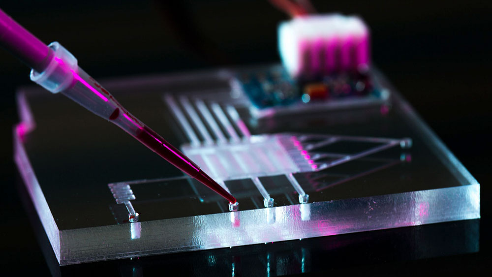 A pipette squirting liquid into a microfluidic device