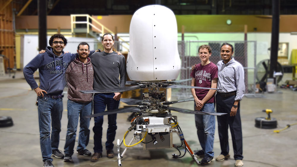 Five engineers stand smiling next to their prototype of a personal flying vehicle.