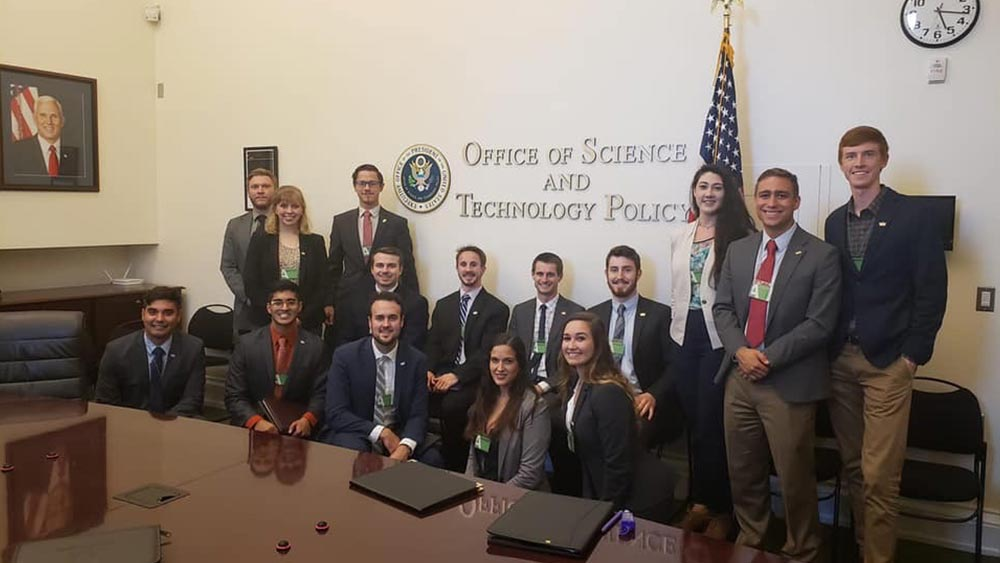 A group of students in business professional attire stand in the Office of Science and Technology Policy