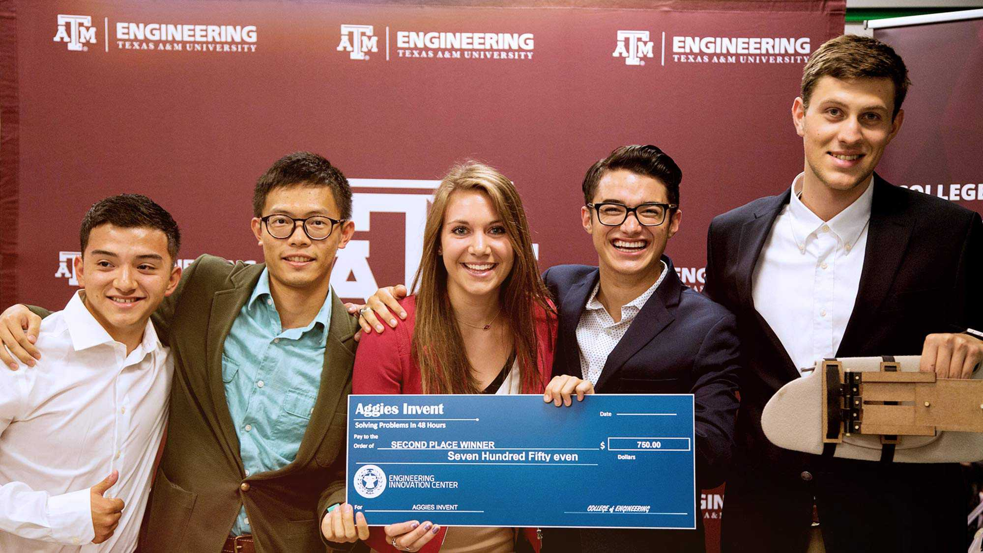 Texas A&M University Engineering 5 student holding each others shoulders holding a check Aggies Invent Solving Problems in 48 hours pay to the order of Second Place Winner Seven Hundred and Fifty Even Dollars Engineering Innovation Center